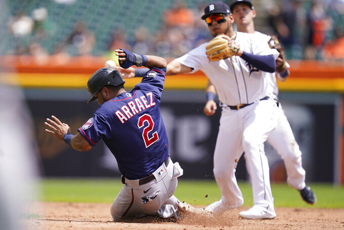 Minnesota Twins' Luis Arraez is out at second as teammate Josh Donaldson hits into a double play during the third inning of the first baseball game of a doubleheader, Saturday, July 17, 2021, in Detroit. (AP Photo/Carlos Osorio)