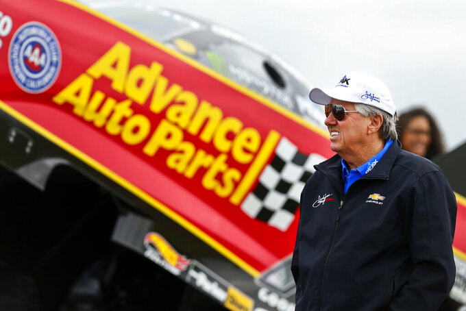 FILE - In this May 21, 2018, file photo, NHRA Funny Car legend John Force paces the staging lanes near his daughter Courtney's car prior to the semifinals of the Menards NHRA Heartland Nationals at Heartland Motorsports Park in Topeka, Kan. More than a half century after he began piloting dragsters, Force, 70, will be in his Funny Car this weekend for the start of a new season in Pomona, Calif. (Chris Neal/The Topeka Capital-Journal via AP, File)