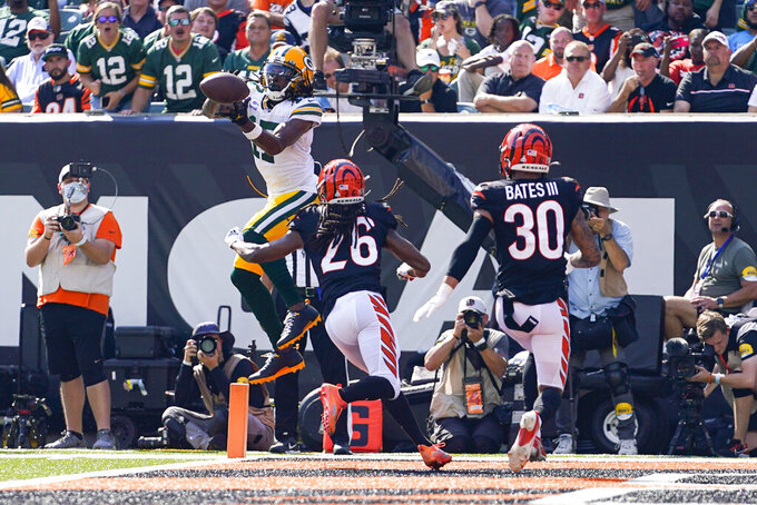 Green Bay Packers wide receiver Davante Adams (17) makes a catch over Cincinnati Bengals cornerback Trae Waynes (26) for a touchdown in the first half of an NFL football game in Cincinnati, Sunday, Oct. 10, 2021. (AP Photo/Bryan Woolston)