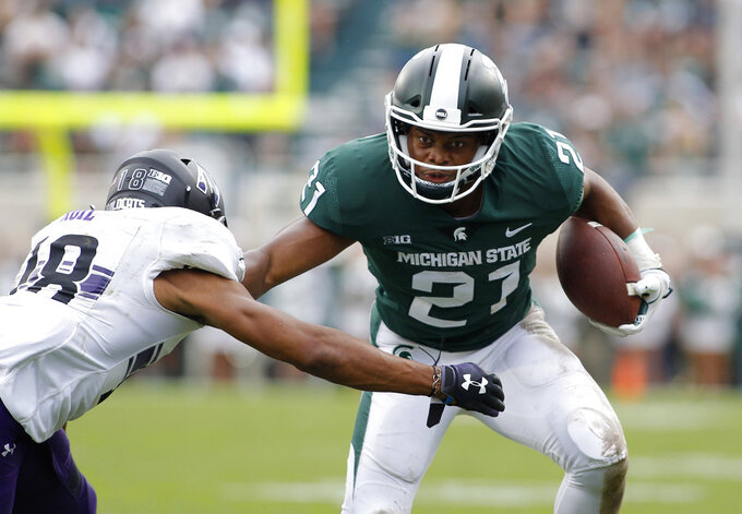 Michigan State's Cam Chambers, right, runs on a pass reception against Northwestern's Cameron Ruiz during the fourth quarter of an NCAA college football game, Saturday, Oct. 6, 2018, in East Lansing, Mich. Northwestern won 29-19. (AP Photo/Al Goldis)