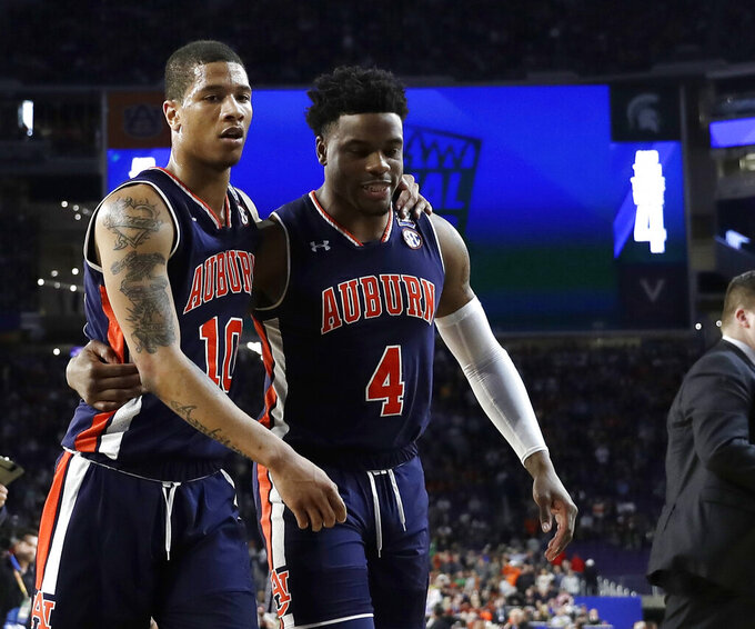 Auburn guard Samir Doughty, left, walks off the court with teammate Malik Dunbar during the first half against Virginia in the semifinals of the Final Four NCAA college basketball tournament, Saturday, April 6, 2019, in Minneapolis. (AP Photo/David J. Phillip)