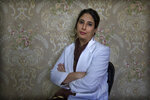 """In this Sept. 27, 2019, photo, a Kashmiri doctor Sabahat Rasool sits for a photograph inside her clinic in Srinagar, Indian controlled Kashmir. Rasool tells the story of a pregnant woman who refused to be admitted in hospital because """"there was no way she could communicate with her family and tell them that she needed to be admitted."""" She was brought in unconscious the next day. """"She survived but lost her unborn baby all because she could not afford to stay back the previous night for fear her family would think she was missing or kidnapped."""" (AP Photo/ Dar Yasin)"""