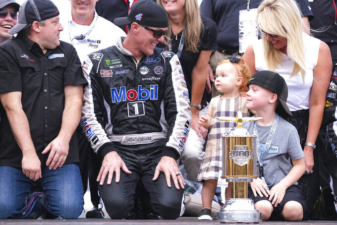 Kevin Harvick, center, is joined by his family, wife DeLana, right, son Keelan,, daughter Piper, and car owner Tony Stewart, left, during the NASCAR Brickyard 400 auto race at Indianapolis Motor Speedway, Sunday, Sept. 8, 2019, in Indianapolis. (AP Photo/AJ Mast)