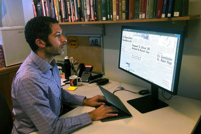 In this Monday, Feb. 24, 2020, photo, Dartmouth College's Matthew Delmont views the website he created, Black Quotidian, in his office on the school's campus in Hanover, N.H. The website is an archive of digitized African-American newspaper content that highlights the lives of every day African-Americans in the 20th century. Many of the people featured were well known in their communities but often were overlooked in African-American history books. (AP Photo/Michael Casey)