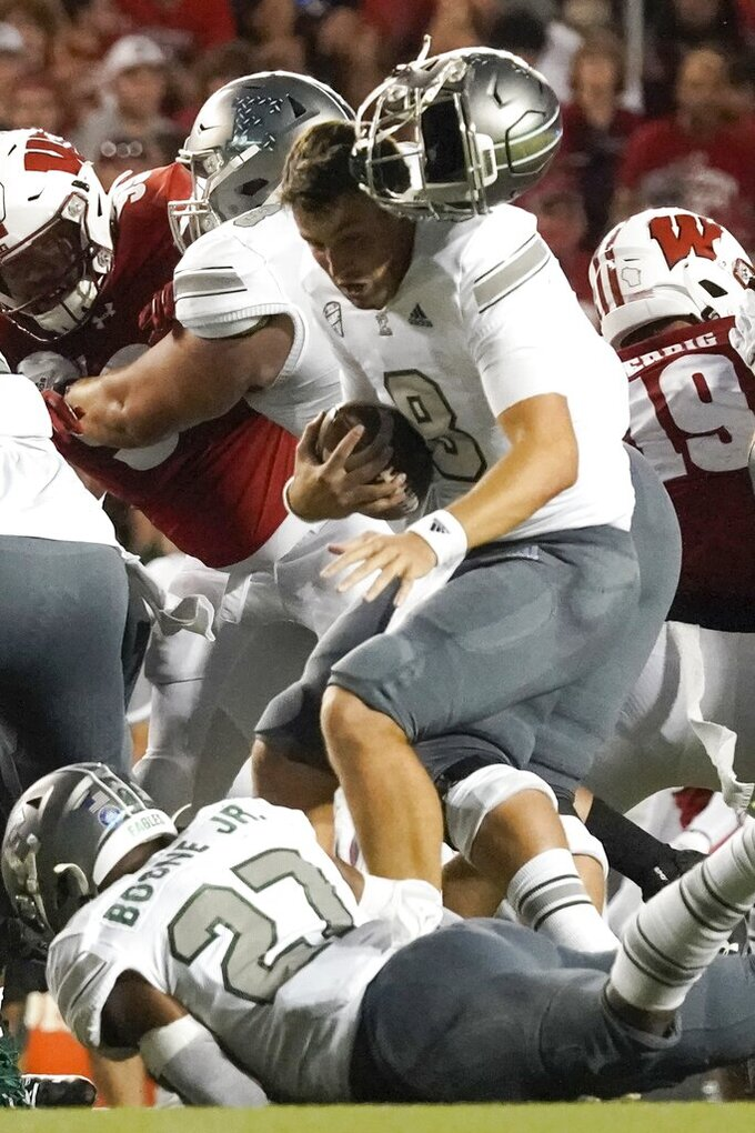 Eastern Michigan quarterback Ben Bryant loses his helmet during the first half of an NCAA college football game against Wisconsin Saturday, Sept. 11, 2021, in Madison, Wis. (AP Photo/Morry Gash)