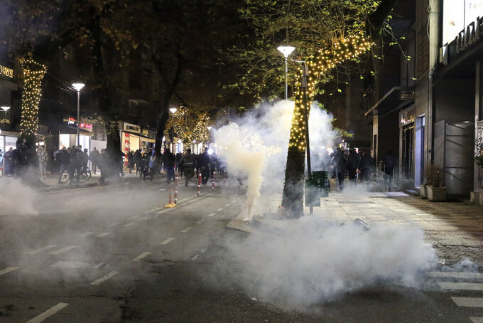 Albanian protesters run away from teargas during a protest rally in Tirana, Saturday, Dec. 12, 2020. Demonstrators in a northern Albanian city damaged the left-wing governing Socialist Party's offices and injured a police officer Saturday, authorities said, as part of ongoing protests this week after a fatal shooting by police enforcing a coronavirus curfew. (AP Photo/Hektor Pustina)