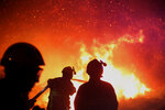 FILE - In this file photo dated Tuesday, July 25, 2017, firefighters spray water as they try to douse a fire near the village of Biguglia, Corsica island, France, as some hundreds of firefighters battle blazes fanned by high winds in more than a dozen zones in the Riviera region of southern France.  European Union experts warn the continent needs to get ready for blazes that reach a massive new scale. (AP Photo/Raphael Poletti, FILE)