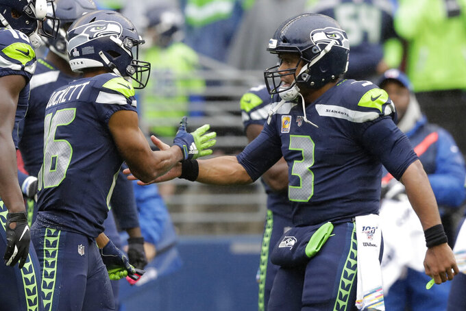 Seattle Seahawks quarterback Russell Wilson (3) greets wide receiver Tyler Lockett (16) after Lockett caught a pass from Wilson for a touchdown against the Baltimore Ravens during the first half of an NFL football game, Sunday, Oct. 20, 2019, in Seattle. (AP Photo/John Froschauer)