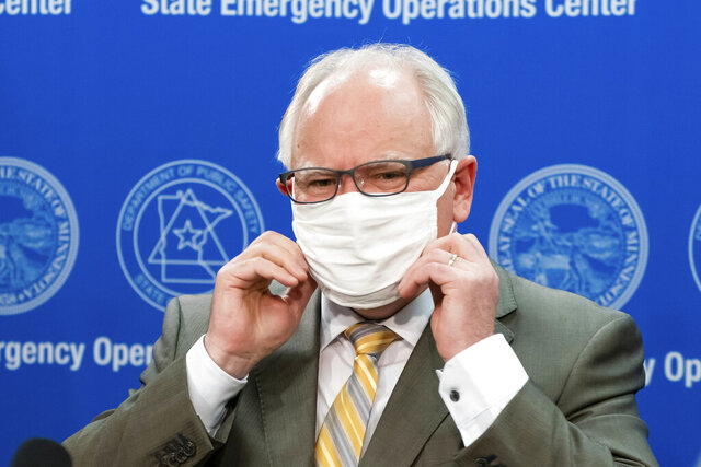 Governor Tim Walz puts his mask back on at the conclusion of the press conference Tuesday, May 5, 2020 with MMB Commissioner Myron Frans to discuss the State of Minnesota's budget projection. The state's budget outlook crumbled from a $1.5 billion surplus to a projected $2.4 billion deficit in just two months, as the COVID-19 pandemic eats up tax revenue and Minnesota leaders accelerate spending to respond.   (Glen Stubbe/Star Tribune via AP, Pool)