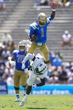 UCLA Bruins quarterback Dorian Thompson-Robinson (1) jumps over Hawaii Warriors defensive back Chima Azunna (0) during the first half of an NCAA college football game Saturday, Aug. 28, 2021, in Pasadena, Calif. (AP Photo/Ashley Landis)