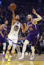 Golden State Warriors' Stephen Curry, left, lays up a shot past Phoenix Suns' Aron Baynes (46) during the first half of an NBA basketball game Wednesday, Oct. 30, 2019, in San Francisco. (AP Photo/Ben Margot)