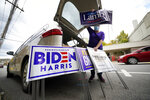 Anne Schirra Baker distributes campaign signs from her car outside the Butler County Democratic Committee headquarters in Butler, Pa., on Thursday, Oct. 15, 2020. Trump signs dominate in conservative Butler County, just north of Pittsburgh, but frustrated Democrats feel a new urgency about expressing themselves. To win Pennsylvania, President Donald Trump's campaign will need big victories across the state in conservative strongholds such as this. (AP Photo/Gene J. Puskar)