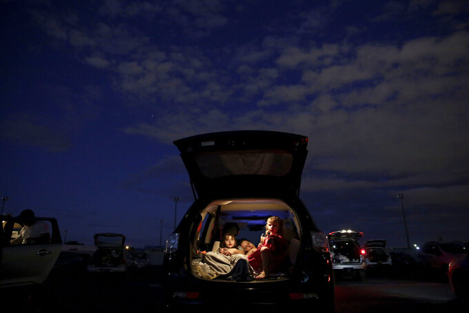 A family watches a movie from the back of their car at a drive-in movie theater where drivers must leave one space empty between them amid the new coronavirus pandemic in Brasilia, Brazil, Saturday, May 23, 2020. The drive-in is 47 years old and one of the only such open-air facilities in operation in Brazil. (AP Photo/Eraldo Peres)