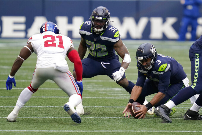 Seattle Seahawks quarterback Russell Wilson (3) tries to pick up the football after he fumbled on a snap against the New York Giants during the first half of an NFL football game, Sunday, Dec. 6, 2020, in Seattle. Giants defensive end Niko Lalos (not shown) recovered the ball on the play. (AP Photo/Elaine Thompson)