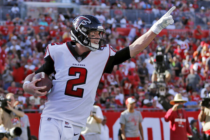 FILE - In this Dec. 30, 2018, file photo, Atlanta Falcons quarterback Matt Ryan (2) celebrates after catching a 5-yard touchdown pass from Mohamed Sanu during the second half of an NFL football game against the Tampa Bay Buccaneers in Tampa, Fla. The Falcons have gained some much-needed salary cap room by restructuring Ryan's contract. The Falcons confirmed that $8.75 million of Ryan's 2019 base salary will be paid as a signing bonus. (AP Photo/Mark LoMoglio, File)