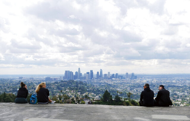 FILE - In this Friday, March 20, 2020 file photo, two pairs of hikers maintain social distance as they mingle at Vista View Point in Griffith Park in Los Angeles as storm clouds pass through. Southern Californians who venture outside this week will see excellent air quality, resulting from business closures during the coronavirus pandemic and recent rain. The area's famous freeway are empty but experts say the lack of cars is contributing only a small amount to the clear skies. (AP Photo/Chris Pizzello, File)