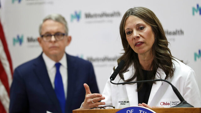In this Feb. 27, 2020 photo, Ohio Department of Health Director Amy Acton gives an update on the state's preparedness and education efforts to limit the potential spread of COVID-19 at MetroHealth Medical Center in Cleveland, as Gov. Mike DeWine listens .Dr. Acton has resigned as Ohio's health director, Gov. Mike DeWine said Thursday, June 11, 2020, capping a contentious few months as the target of frustrations during the coronavirus pandemic that included gun-carrying critics showing up at her home. AP Photo/Tony Dejak)