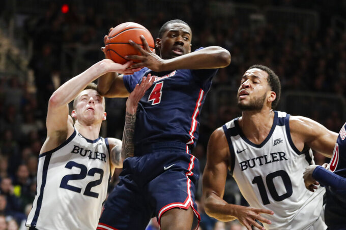 St. John's guard Greg Williams Jr. (4) grabs a rebound over Butler forward Sean McDermott (22) and forward Bryce Nze (10) during the first half of an NCAA college basketball game in Indianapolis, Wednesday, March 4, 2020. (AP Photo/Michael Conroy)