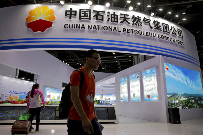 In this Sept. 21, 2016, photo, visitors walk by the China National Petroleum Corporation (CNPC) exhibition booth during the China International Chemical Industry Fair in Shanghai, China. China's government expressed hope Tuesday, July 16, 2019, that Malaysia's dispute with a state-owned Chinese company building two multi-billion-dollar gas pipeline projects can be resolved through