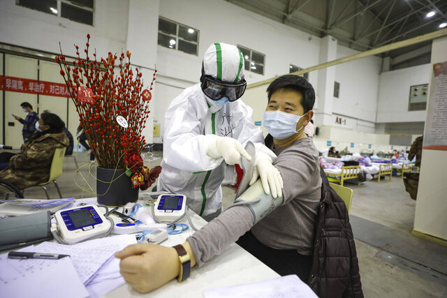 In this Feb. 18, 2020, photo, a medical staff member attends to a COVID-19 patient in a temporary hospital converted from an exhibition center in Wuhan in central China's Hubei province. The hospital, one of the dozen of its kind built in Wuhan, hosts COVID-19 patients with mild symptoms. (Chinatopix Via AP) CHINA OUT