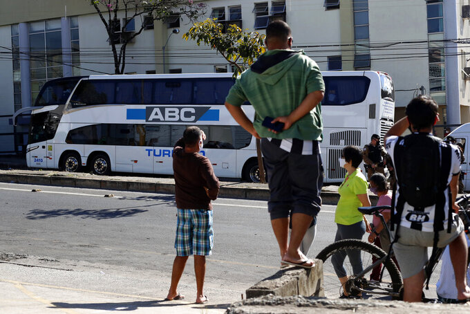 People look at a bus, carrying Argentina's Boca Juniors soccer team, parked outside a police station in Belo Horizonte, Brazil, Wednesday, July 21, 2021, the morning after the team was eliminated from the Copa Libertadores tournament which ended in a brawl and destruction in the locker room. (AP Photo/Bruna Prado)
