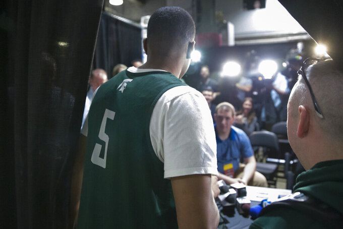 Michigan State guard Cassius Winston (5) arrives to take his seat for an NCAA men's college basketball individual news conference in Washington, Saturday, March 30, 2019. Michigan State plays Duke in the East Regional final game on Sunday. (AP Photo/Alex Brandon)