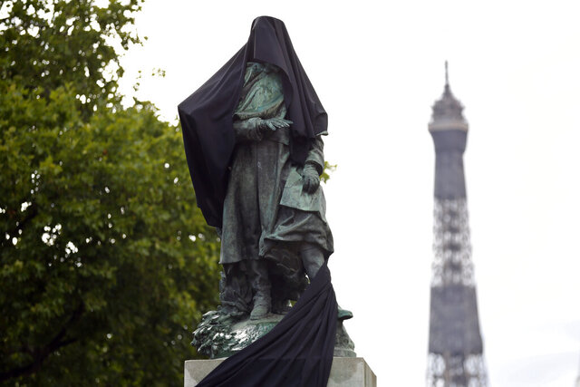 French military commander Joseph Gallieni statue is covered with a black cloth during an action held by anticolonial activists, in Paris, Thursday, June 18, 2020. Gallieni began a colonial career at the end of the 19th century and later played an important role during First World War as a military governor of Paris. Gallieni used brutal methods to quell rebellion of local populations in French colonies, including as a governor of Madagascar where he abolished the 350-year-old monarchy on the island. (AP Photo/Thibault Camus)
