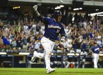 Milwaukee Brewers' Yasmani Grandal celebrates after hitting a three-run home run during the seventh inning of a baseball game against the Minnesota Twins Tuesday, Aug. 13, 2019, in Milwaukee. (AP Photo/Morry Gash)