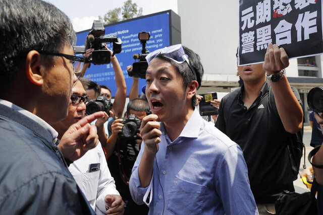 FILE - In this Aug. 12, 2019, file photo, pro-democracy lawmaker Ted Hui, center, argues with pro-Beijing lawmaker Junius Ho, left, during a demonstration in Hong Kong. Hui who is currently visiting Denmark urged European nations on Wednesday to allow protesters in Hong Kong