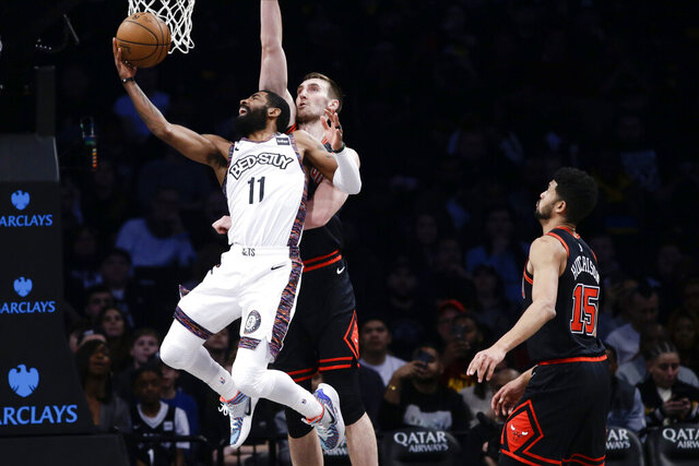 Brooklyn Nets' Kyrie Irving (11) drives past Chicago Bulls' Luke Kornet and Chandler Hutchison (15) during the first half of an NBA basketball game Friday, Jan. 31, 2020, in New York. (AP Photo/Frank Franklin II)