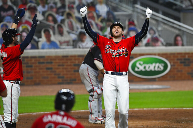 "FILE - In this Sept. 4, 2020, file photo, Atlanta Braves' Freddie Freeman celebrates as he crosses home plate after hitting a grand slam to center field during the fourth inning of the second baseball game of the team's doubleheader against the Washington Nationals in Atlanta. Freeman easily won the NL MVP award Thursday, Nov. 12, topping off a trying year that saw him become so ill with COVID-19 he prayed ""please don't take me."" (AP Photo/John Amis, File)"