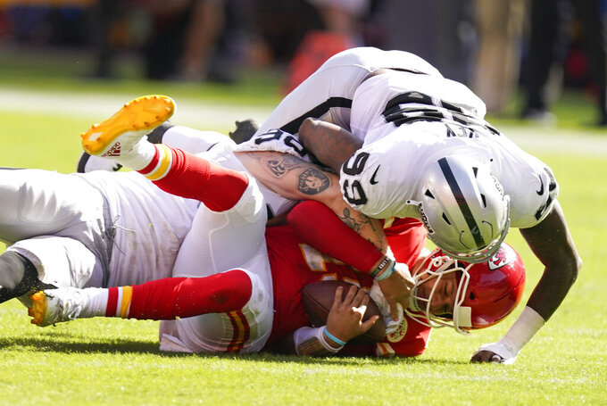 Kansas City Chiefs quarterback Patrick Mahomes, center, is sacked by Las Vegas Raiders defensive end Maxx Crosby, rear and defensive end Arden Key (99) during the second half of an NFL football game, Sunday, Oct. 11, 2020, in Kansas City. (AP Photo/Charlie Riedel)