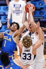 BYU center Richard Harward (42) grabs a rebound as teammate Caleb Lohner (33) and UCLA guard Jules Bernard (1) close in during the second half of a first-round game in the NCAA college basketball tournament at Hinkle Fieldhouse in Indianapolis, Saturday, March 20, 2021. (AP Photo/AJ Mast)