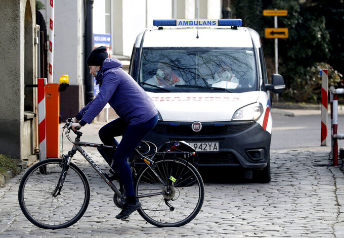 A cyclist passes in front of an ambulance by an infectious diseases hospital in Warsaw, Poland, on Thursday, March 25, 2021. Amid a sharp spike in new infections and hospitalizations that are bringing the health care to its limits, Poland has stepped up pandemic measures for two weeks starting Saturday, including fewer people to be allowed into churches at the holiday time. (AP Photo/Czarek Sokolowski)