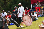 A man carries a cardboard cutout of Atlanta Falcons quarterback Matt Ryan (2) as he and about 1,000 people watch during Falcons NFL training camp football practice Saturday, July 31, 2021, in Flowery Branch, Ga. (AP Photo/John Bazemore)