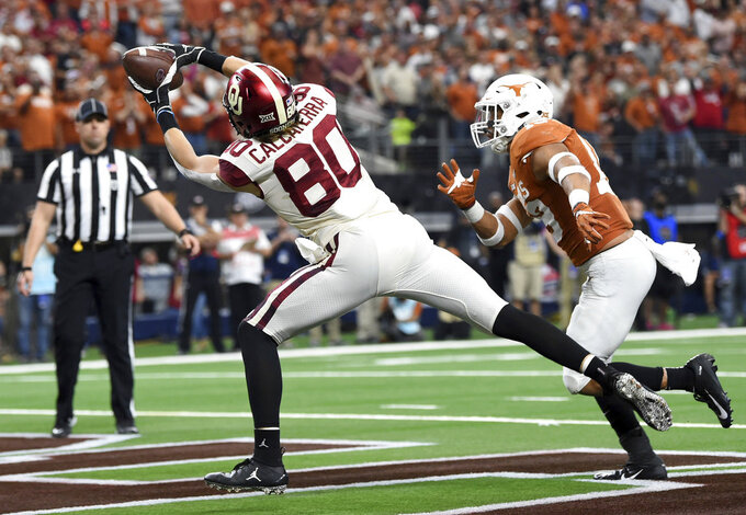 Oklahoma tight end Grant Calcaterra (80) hauls in a touchdown pass from quarterback Kyler Murray in front Texas defensive back Brandon Jones during the first half of the Big 12 Conference championship NCAA college football game on Saturday, Dec. 1, 2018, in Arlington, Texas. (AP Photo/Jeffrey McWhorter)