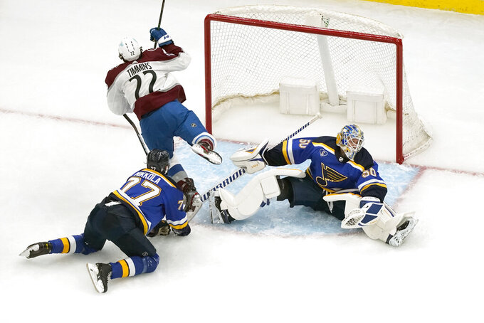 St. Louis Blues goaltender Jordan Binnington, right, makes a save on a shot by Colorado Avalanche's Conor Timmins (22) as Blues' Niko Mikkola (77) defends during the second period in Game 4 of an NHL hockey Stanley Cup first-round playoff series Sunday, May 23, 2021, in St. Louis. (AP Photo/Jeff Roberson)