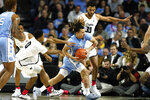 North Carolina's guard Cole Anthony (2) works to control the ball with Wake Forest's Brandon Childress (0) and Olivier Sarr (30) guarding in the first half of an NCAA college basketball game Tuesday, Feb. 11, 2020 in Winston-Salem, N.C. (AP Photo/Lynn Hey)
