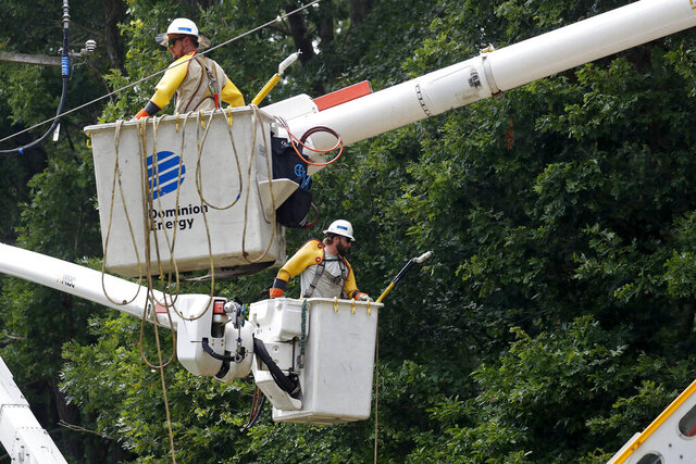 Andrew Dodson, left, and Scott Crane, of Dominion Energy work to repair a fallen electrical line near Newsome Drive in York County, Va. Wednesday afternoon, Aug. 5, 2020 after multiple trees were toppled by Tropical Storm Isaias. Power would be restored to more than 700 customers once the work was completed. (Jonathon Gruenke/The Daily Press via AP)