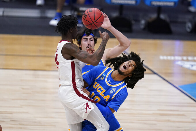 Alabama guard Keon Ellis (14) collides with UCLA guard Tyger Campbell (10) in the first half of a Sweet 16 game in the NCAA men's college basketball tournament at Hinkle Fieldhouse in Indianapolis, Sunday, March 28, 2021. (AP Photo/Michael Conroy)