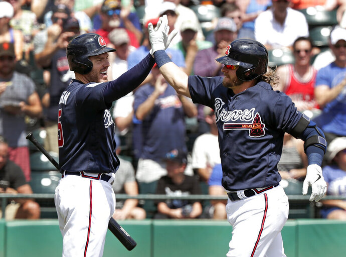 FILE - In this March 15, 2019, file photo, Atlanta Braves' Josh Donaldson, right, gets a high-five from teammate Freddie Freeman after hitting a two-run home run in the third inning against the Miami Marlins in a spring baseball exhibition game in Kissimmee, Fla. Freeman believes the Phillies, Nationals and Mets had busy offseasons because they wanted to catch up to the 2018 NL East champion Braves. (AP Photo/John Raoux, File)