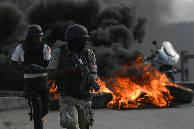 Armed police take cover near a barricade set on fire by protesters demanding justice for the assassinated President Jovenel Moise stands, in Cap-Haitien, Haiti, Thursday, July 22, 2021. Demonstrations after a memorial service for Moise turned violent on Thursday afternoon with protesters shooting into the air, throwing rocks and overturning heavy concrete barricades next to the seashore as businesses closed and people took cover. (AP Photo/Matias Delacroix)