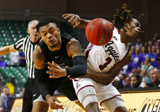 Grand Canyon's Carlos Johnson, left, fouls New Mexico State guard Terrell Brown as he tries to pick off a pass during an NCAA college basketball game for the Western Athletic Conference men's tournament championship Saturday, March 16, 2019, in Las Vegas. (AP Photo/Steve Marcus)
