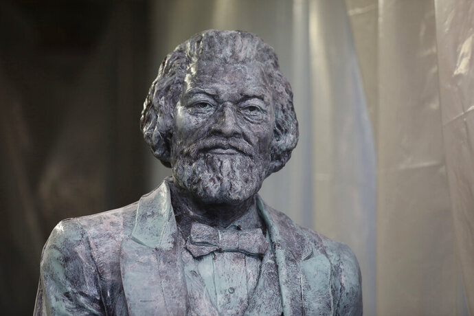 A replica of a statue of Frederick Douglass sits in the studio of Olivia Kim, a sculptor who worked on finishing three replicas, July 16, 2018 in her Rochester, N.Y. studio. A statue of abolitionist Frederick Douglass has been ripped from its base in Rochester on the anniversary of one of his most famous speeches. Police say the statue of Douglass was taken from Maplewood Park and placed near the Genesee River gorge on Sunday, July 5, 2020. (Tina MacIntyre-Yee/Democrat & Chronicle via AP)
