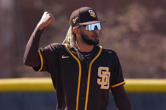 San Diego Padres' Fernando Tatis Jr. reacts after making a catch during spring training baseball practice Saturday, Feb. 27, 2021, in Peoria, Ariz. (AP Photo/Charlie Riedel)