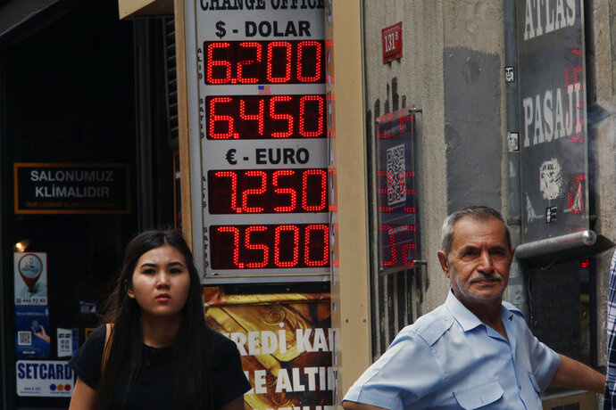People stand outside an exchange office in Istiklal Avenue, the main shopping road in Istanbul, Thursday, Sept. 13, 2018. Turkey's central bank on Thursday raised its key interest rate sharply to contain inflation and support the currency after steep declines this year, despite President Recep Tayyip Erdogan's comments earlier opposing any rate hikes. The currency had plunged some 40 percent against the dollar this year.(AP Photo/Lefteris Pitarakis)