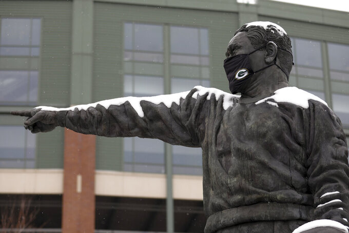"""A statue of former football player and coach Earl Louis """"Curly"""" Lambeau sports a face mask and fresh coat of snow before the NFC championship NFL football game between the Tampa Bay Buccaneers and Green Bay Packers in Green Bay, Wis., Sunday, Jan. 24, 2021. (AP Photo/Mike Roemer)"""