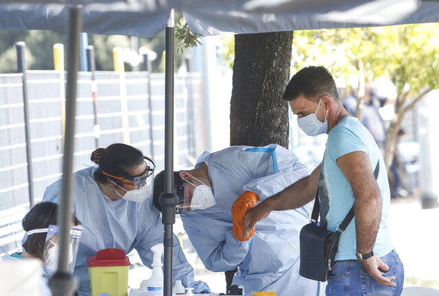 A passenger of a bus coming from Romania, right, undergoes a voluntary Covid-19 blood test, at the Tiburtina bus station, in Rome, Wednesday, July 29, 2020. The Lazio region, which includes Rome, is beginning voluntary tests on passengers arriving in Italy from Romania, Bulgaria and Ukraine, with a blood test on finger with results in 8 minutes followed by swab test if result is positive. (AP Photo/Riccardo De Luca)