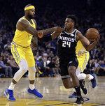Sacramento Kings' Buddy Hield (24) drives against Golden State Warriors' DeMarcus Cousins, left, during the first half of an NBA basketball game Thursday, Feb. 21, 2019, in Oakland, Calif. (AP Photo/Ben Margot)