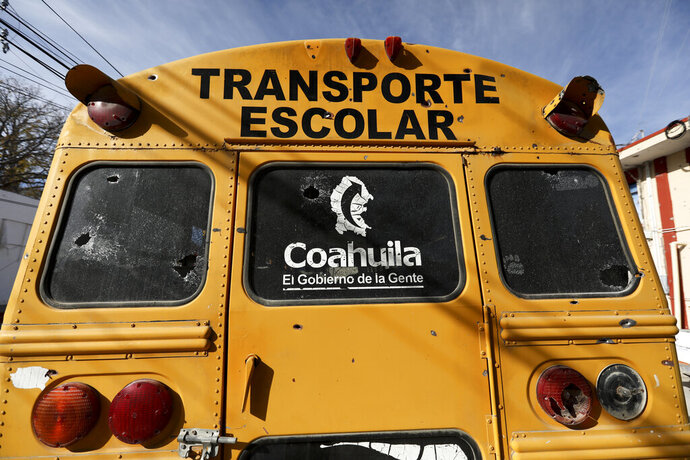 A school bus with bullet holes sits parked outside City Hall in Villa Union, Mexico in Monday, Dec. 2, 2019. The small town near the U.S.-Mexico border began cleaning up Monday even as fear persisted after 22 people were killed in a weekend gunbattle between a heavily armed drug cartel assault group and security forces. (AP Photo/Eduardo Verdugo)
